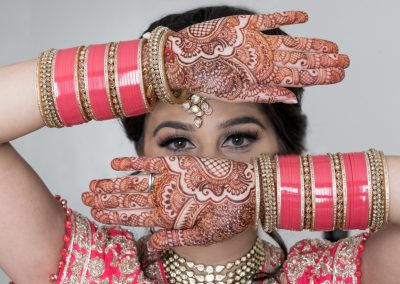 Indian bride looking through henna hands